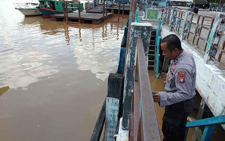 Anggota Pos Polisi Pelabuhan Rambang Aipda Toto Santoso mengecek ketinggian debit air Sungai Kahayan, Selasa, 30 April 2019.