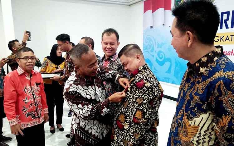 Ketua DPRD Barito Utara Set Enus Y Mebas menerima pin emas dari Ketua Umum PWI Pusat H Atal S Depari