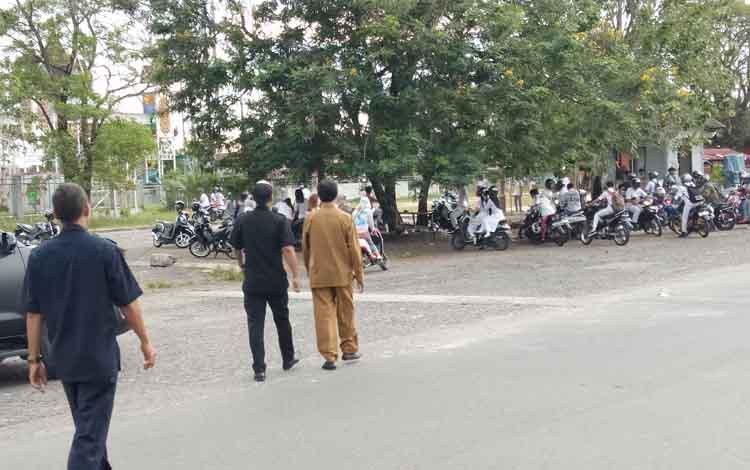 Plt Kepala SMAN 1 Palangka Raya, M Ramli (pakaian cokelat) berjalan mendatangi siswa yang berkumpul di seberang sekolah tersebut, Senin, 13 Mei 2019