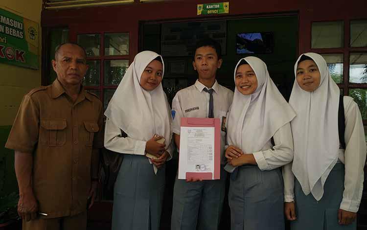 Frengki Banjarnahor (tengah) siswa peringkat kelima nilai Fisika tertinggi di Kalteng.
