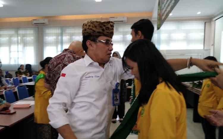 Rektor UPR Andrie  Elia memakaikan selempang simbolis penerima beasiswa Peduli Orangutan 2019, Rabu, 15 Mei 2019