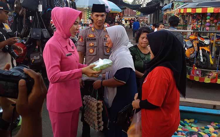 Kapolres Bartim AKBP Zulham Effendi didampingi istrinya Yanti Zulham Effendi, membagikan takjil kepada masyarakat, Kamis, 16 Mei 2019.