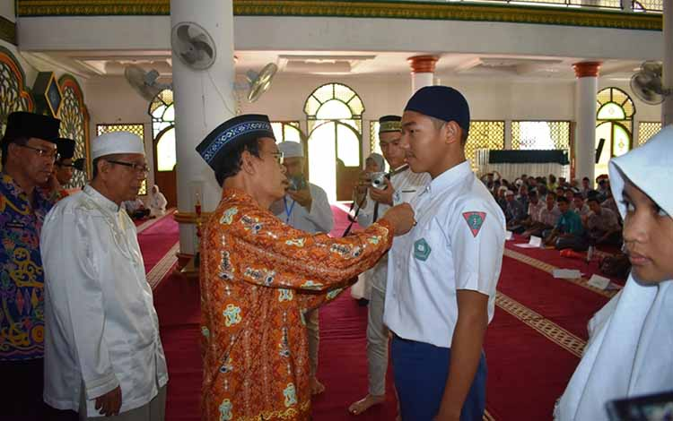 Wakil Bupati Kapuas Nafiah Ibnor saat menyematkan tanda peserta Pesantren Ramadan di Mesjid Al Mukarram Amanah pada Kamis, 16 Mei 2019