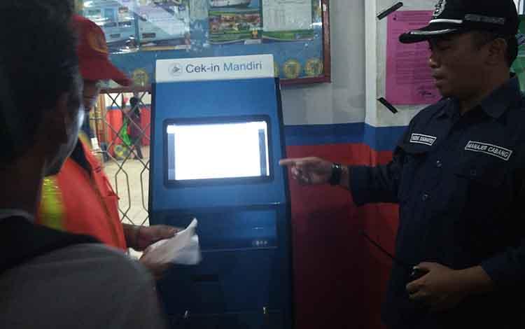 Manager PT DLU cabang Sampit Hendrik Sugiharto saat melayani penumpang yang hendak check-in menggunakan mesin check-in mandiri di Pelabuhan Sampit, Senin, 21 Mei 2019.
