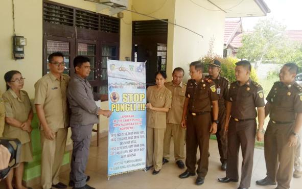 Tim saber pungli menyerahkan spanduk untuk tidak melakukan pungli di SDN 7 Panarung, Kota Palangka Raya, Selasa, 21 Mei 2019.