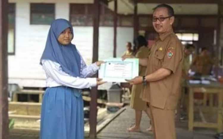 Kepala SMAN 1 Katingan Tengah Iskardi memberikan piagam penghargaan kepada Arifa Pratiwi Nugraheni,