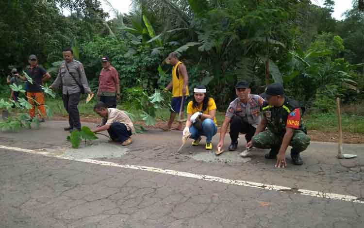 Sejumlah personel Polsek Cempaga Hulu, pegawai Kecamatan Cempaga Hulu dan warga, saat memerbaiki Jalan Tjilik Riwut Km 56, Jumat, 24 Mei 2019.