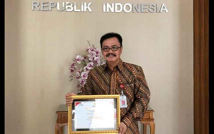 Kepala Dinas Komunikasi dan Informasi Provinsi Kalimantan Tengah, Herson B. Aden memegang penghargaan Keterbukaan Informasi Publik.