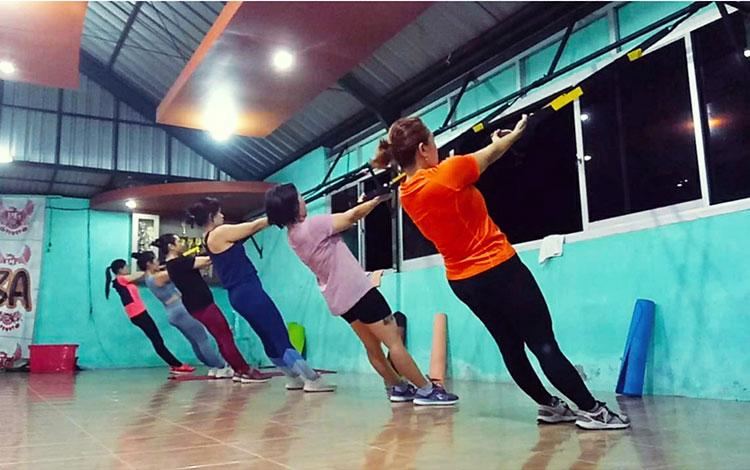 Peserta senam di pusat kebugaran melakukan gerakan suspension workout.
