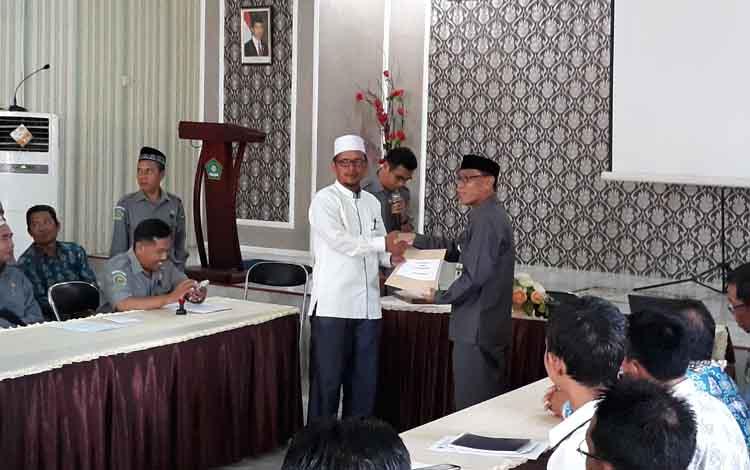 Kepala Kemenag Kapuas Ahmad Bahruni menyerahkan secara simbolis hasil Ujian Nasional kepada salah seorang kepala MTs, Selasa, 28 Mei 2019.