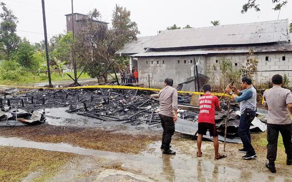 Petugas memasang garis polisi di area bangunan barak yang hangus terbakar di Jalan Manduhara, Blok C, Kelurahan Kereng Bangkirai, Kecamatan Sabangau, Kota Palangka Raya, Kamis, 6 Juni 2019.