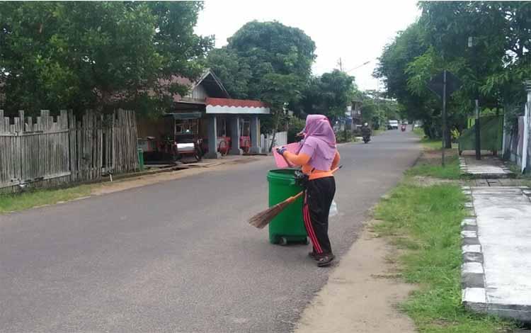 Petugas ketika membersihkan sampah di sepanjang jalan Gatot Subroto Kuala Pembuang, Selasa 11 Juni 2019