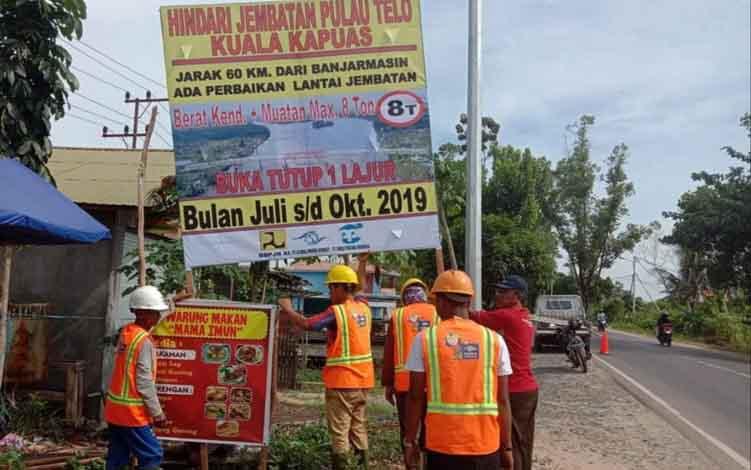 Petugas saat melakukan pemasangan papan sosialisasi atau pemberitahuan buka tutup satu jalur jembatan Pulau Telo Kapuas di Jalan Trans Kalimantan Anjir.