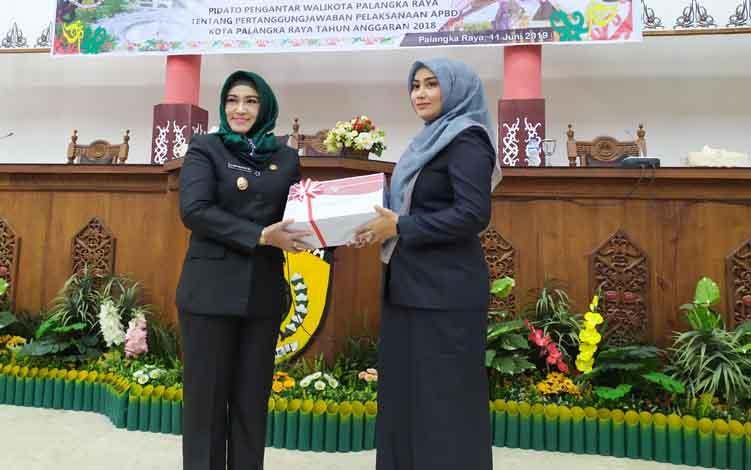 Wakil Wali Kota Palangka Raya, Hj Umi Mastikah menyerahkan dokumen Pertanggungjawaban APBD 2018 kepada Wakil Ketua I DPRD, Ida Ayu Nia Anggraini, Selasa, 11 Juni 2019.