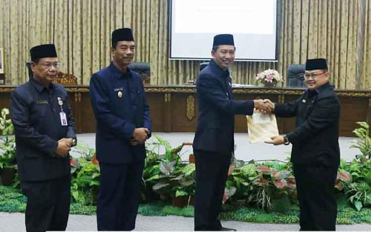 Bupati Barito Utara, Nadalsyah menyerahkan pidato pengantar bupati ke Ketua DPRD, Set Enus Y Mebas.
