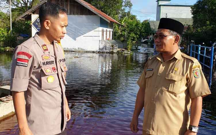 Plt Kepala BPBD Kabupaten Katingan, Akhmad Rubama dan Kapolsek Katingan Hilir saat meninjau banjir di Kasongan.
