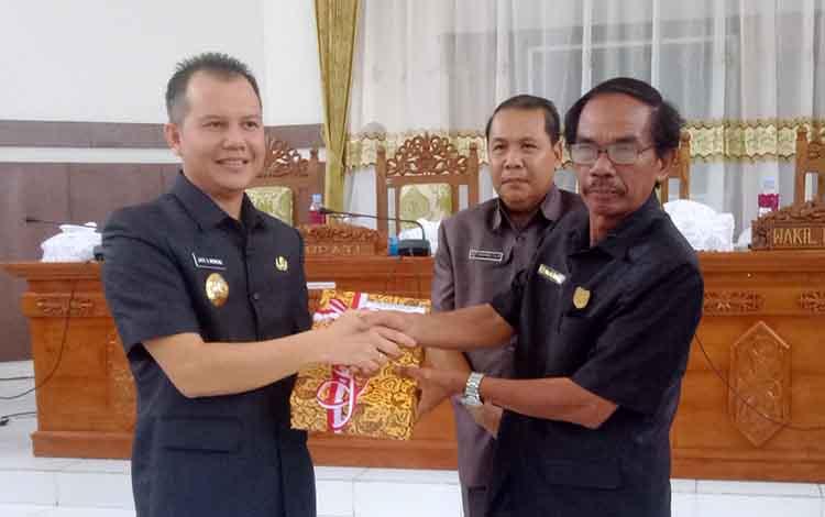 Bupati Gunung Mas, Jaya S Monong (kanan) menyampaikan raperda kepada Ketua DPRD Kabupaten Gu