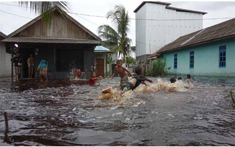Anak-anak RT 2 Desa Sungai Kapitan bermain air saat banjir