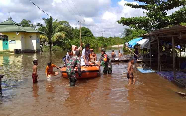 Personel Koramil 1013-07/Puruk Cahu bersama BPBD Murung Raya saat membantu warga Desa Bahitom melewati banjir, Senin, 17 Juni 2019.