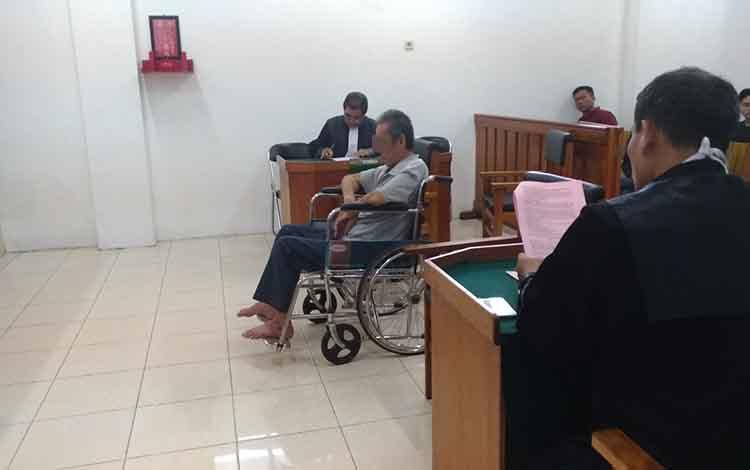 LS, saat mengikuti persidangan di Pengadilan Negeri dengan kursi rodanya.