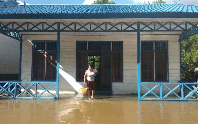 Seorang warga saat berada di teras rumahnya yang sudah mulai terendam banjir, kemaren. Saat ini beberapa desa di Kecamatan Bukit Santuai sudah terendam banjir.