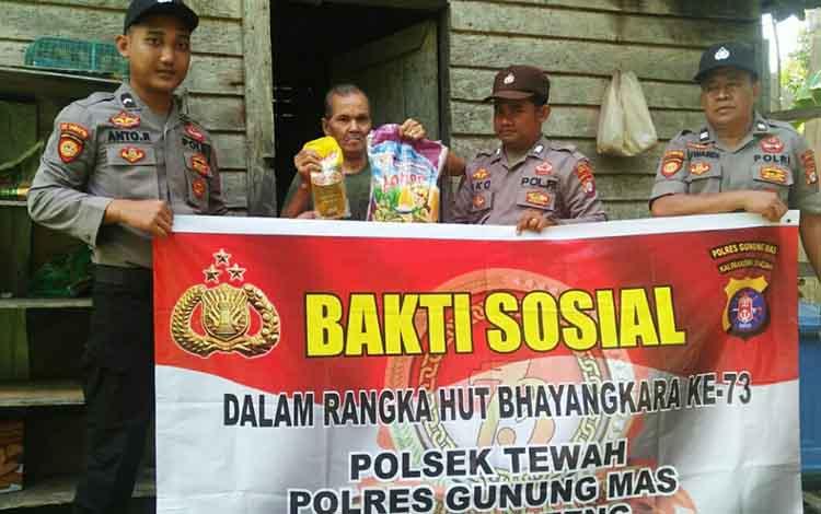 Anggota Bhabinkamtibmas Polsek Tewah menyerahkan paket sembako