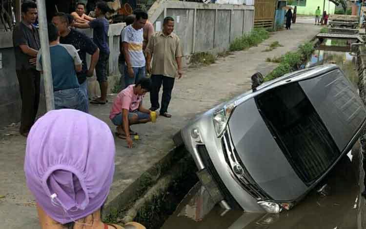 Sejumlah warga saat melihat kondisi mobil yang masuk ke dalam parit, Selasa, 25 Juni 2019.