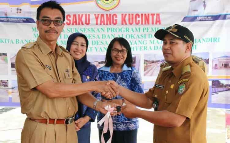 Wakil Bupati Barito Utara, Suganto Panala Putra menyerahkan kunci mobil ambulans kepada Pj Kades Tawan Jaya, Roby.
