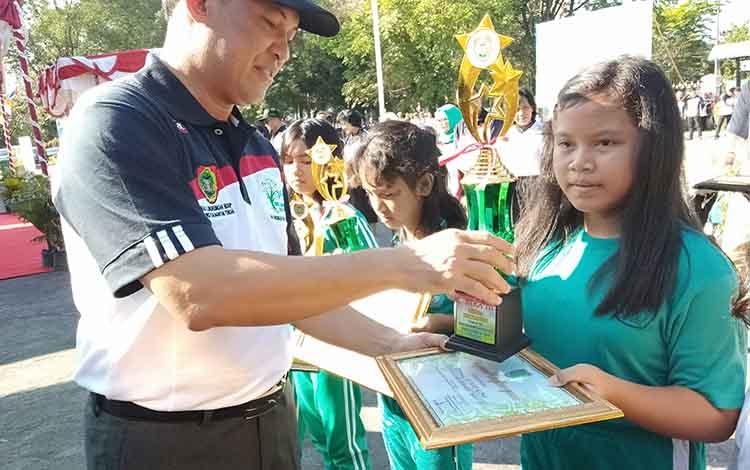 Sekda Kalteng Fahrizal Fitri menyerahkan piala dan piagam penghargaan kepada murid SD, Jumat, 28 Juni 2019.