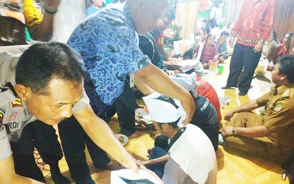 Camat Teweh Baru, Ketua DAD Barito Utara, Damang, anggota Polri dan TNI ,saat memasangkan laung kandong atau laung matei kepada keluarga yang mengadakan ritual Wara Desa Hajak, Kecamatan Teweh Baru, Senin, 1 Juli 2019.