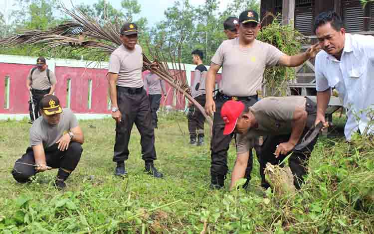 Kapolres Sukamara, AKBP Sulistiyono bersama anggotanya saat membersihkan rumah adat di Desa Natai Sedawak.