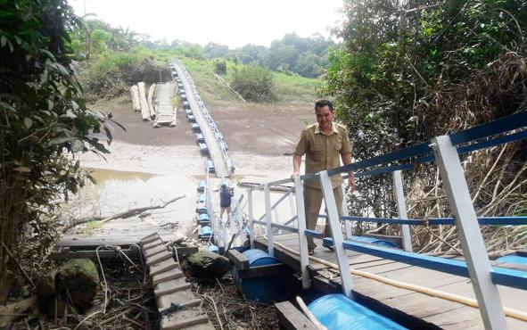 Sekretaris Desa Nihan Hilir Arbino saat menujukkan jembatan darurat yang dibangun Pemkab Barito Utara.