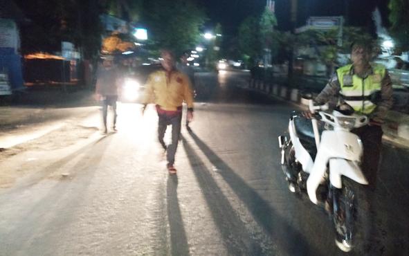 Aparat kepolisian saat mendorong motor yang digunakan untuk balap liar, Minggu, 7 Juli 2019 dini hari.