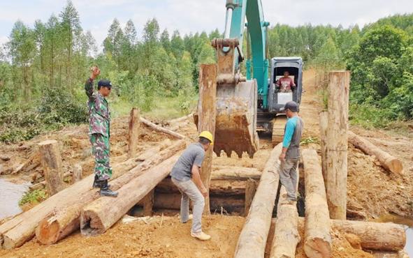 Anggota Kodim 1014/Pangkalan Bun, Kabupaten Kobar, bersama masyarakat bergotong royong membangun jembatan pada program TMMD yang ke-105, Minggu, 7 Juli 2019.
