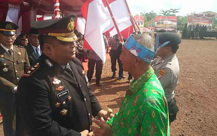 Ismaun Marsone Gatan saat berjabat tangan dengan Kapolres Kotim AKBP Mohammad Rommel, pada upacara peringatan Hari Bhayangkara di Kecamatan Parenggean, Rabu, 10 Juli 2019.