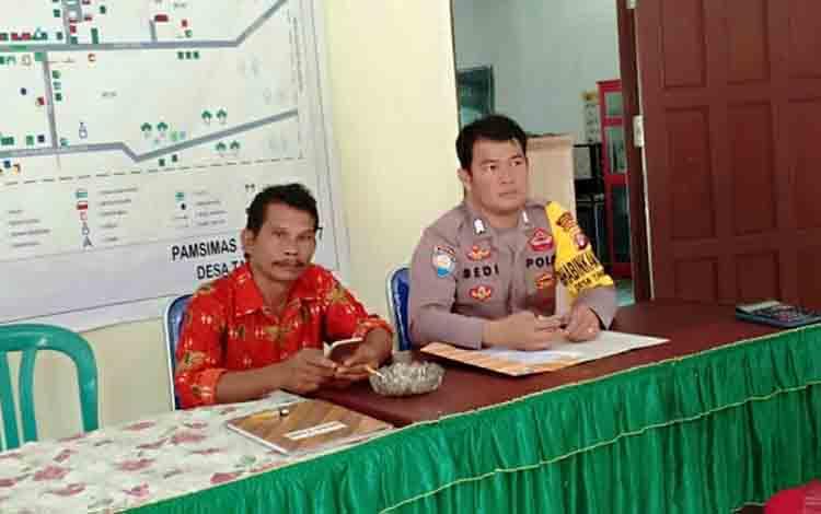 Bhabinkamtibmas Polsek Kurun, Brigpol Bedi berbincang dengan Sekdes Tanjung Riu, Iwan Yani terkait DD dan ADD tahap I Desa Tanjung Riu