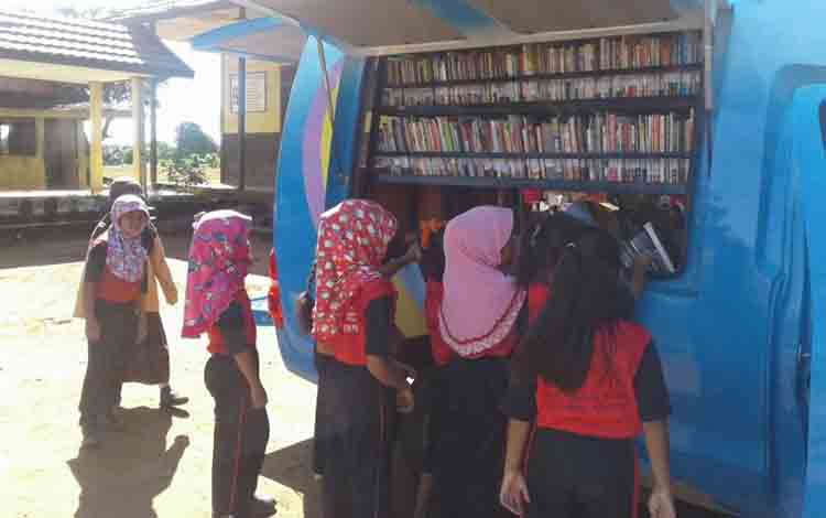 Anak-anak Desa Bukit Sungkai Kecamatan Balai Riam Kabupaten Sukamara saat memilih buku di mobil perpustakaan keliling.
