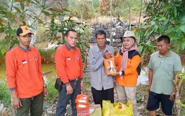 Personel BPBD Kapuas saat menyerahkan bantuan kepada korban kebakaran di Desa Mawar Mekar, Kecamatan Pulau Petak, Jumat, 12 Juli 2019.