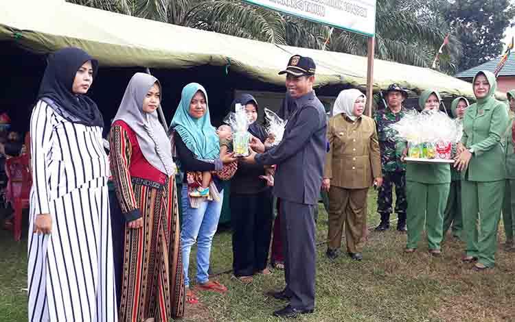 Ketua DPRD Kotawaringin Barat, Triyanto memberikan susu formula pada upacara pembukaan TMMD