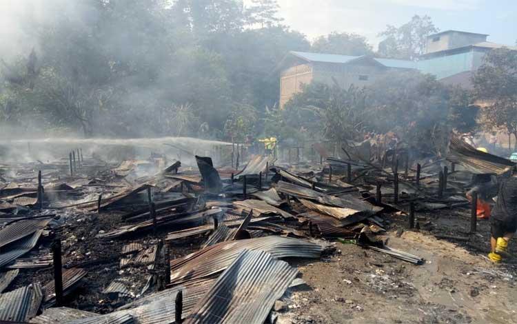 Petugas pemadam terus menyiram sisa api yang telah menghaguskan barak 10 pintu, 2 rumah beserta sarang burung walet