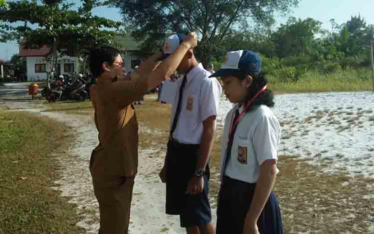 Kepala SMAN 2 Banama Tingang menyerahkan tanda peserta kepada peserta MPLS pada hari pertama sekolah.