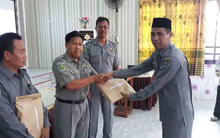 Kasi Pendidikan Madrasah Kemenag Kapuas Sajarwan menyerahkan blangko Ijazah kepada Kepala MTsN 1 Kapuas Arbainsyah, Selasa, 16 Juli 2019.