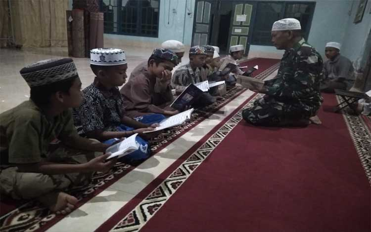 Sersan Satu Junaidi menegajari anak-anak membaca Alquran