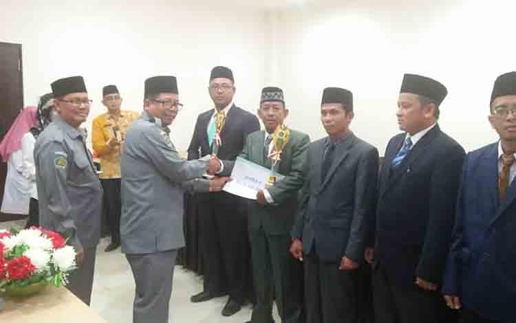 Kepala Kanwil Kemenag Kalteng Masrawan menyerahkan penghargaan kepada Kepala KUA Tamban Catur Ahyadi di Kota Palangka Raya, Selasa, 16 Juli 2019.