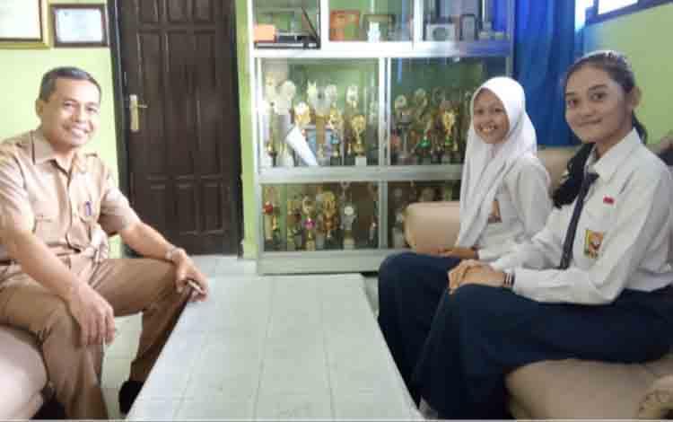 Kepala SMKN 1 Pangkalan Bun bersama Faiza Zahri dan Claudia Florenza Lola Ananta siswa baru yang diterima melalui jalur prestasi