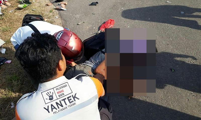 Seorang korban kecelakaan saat tergeletak di jalan dan dibantu oleh warga sekitar