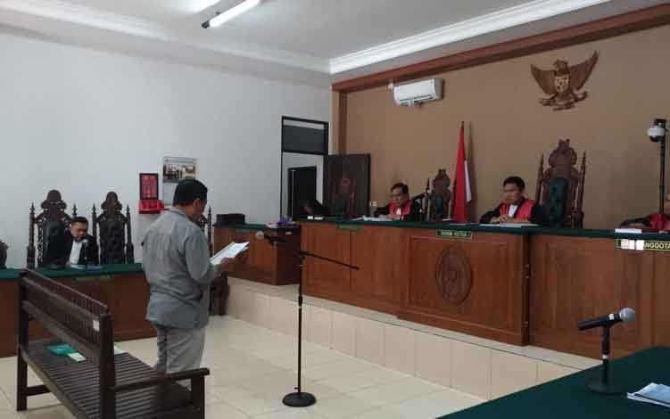 Akhmad Yantenglie berdiri saat membacakan pleoi di hadapan majelis hakim Pengadilan Tipikor Palangka Raya, Kamis, 18 Juli 2019.