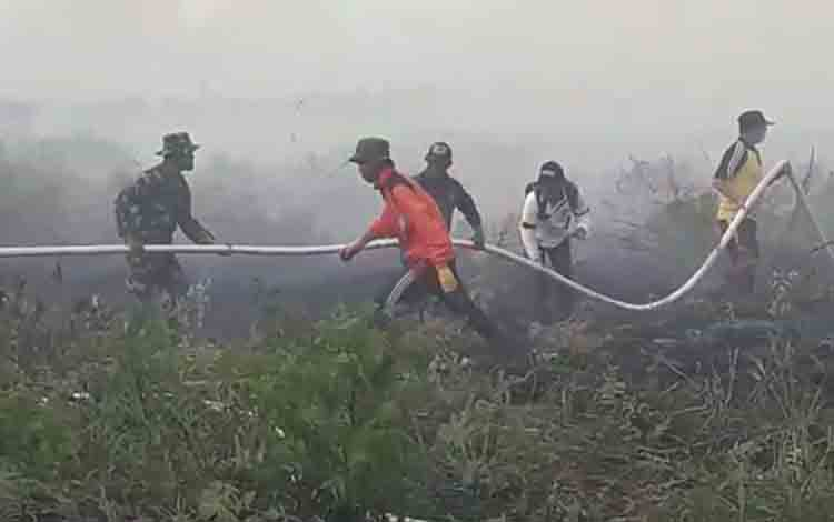 Sejumlah anggota Satgas Karhutla saat memadamkan kebakaran lahan.