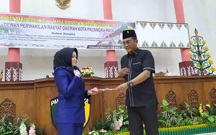 Ketua DPRD Kota Palangka Raya, Sigit K Yunianto menyerahkan berkas tiga raperda inisiatif DPRD kepada Wakil Wali Kota Palangka Raya, Hj Umi Mastikah, Kamis, 18 Juli 2019.