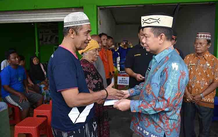 Bupati Kapuas Ben Brahim S Bahat menyerahkan bantuan kepada korban kebakaran di Jalan Tjilik Riwut, Kelurahan Selat Dalam, Kecamatan Selat pada Jumat, 19 Juli 2019.